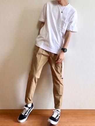 Comment s'habiller à l'adolescence: Associe un t-shirt à col rond blanc avec un pantalon chino marron clair pour une tenue idéale le week-end. Une paire de des baskets basses en toile noires et blanches est une option parfait pour complèter cette tenue.