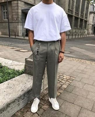 Comment porter un pantalon chino gris: Essaie d'harmoniser un t-shirt à col rond blanc avec un pantalon chino gris pour une tenue confortable aussi composée avec goût. Cet ensemble est parfait avec une paire de baskets basses en cuir blanches et noires.