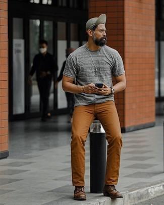 Comment porter un pantalon chino tabac: Pense à associer un t-shirt à col rond gris avec un pantalon chino tabac pour une tenue confortable aussi composée avec goût. D'une humeur créatrice? Assortis ta tenue avec une paire de bottes de loisirs en cuir marron foncé.