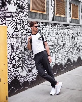 Comment porter: t-shirt à col rond imprimé blanc et noir, pantalon chino gris foncé, chaussures de sport blanches, sac à dos en cuir noir
