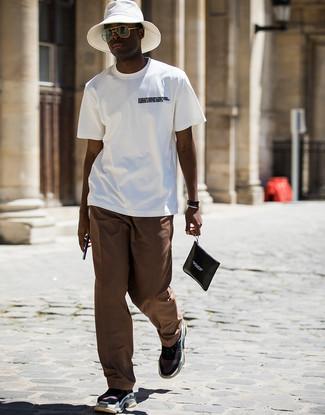 Comment porter: t-shirt à col rond imprimé blanc et noir, pantalon chino marron, chaussures de sport noires, pochette en cuir imprimée noire et blanche