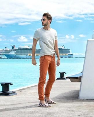 Comment porter: t-shirt à col rond blanc, pantalon chino orange, espadrilles en toile à rayures horizontales blanches, ceinture en toile tressée blanche