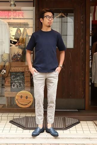 Comment porter un pantalon chino en lin beige: Pense à harmoniser un t-shirt à col rond bleu marine avec un pantalon chino en lin beige pour un déjeuner le dimanche entre amis. Une paire de des slippers en cuir bleu marine ajoutera de l'élégance à un look simple.