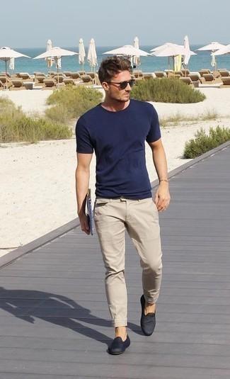 Comment porter un pantalon chino marron clair: Opte pour un t-shirt à col rond bleu marine avec un pantalon chino marron clair pour un look de tous les jours facile à porter. Habille ta tenue avec une paire de des slippers en toile bleu marine.