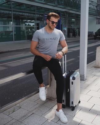 Comment porter: t-shirt à col rond imprimé gris, pantalon de jogging noir, baskets basses en cuir blanches, valise argentée