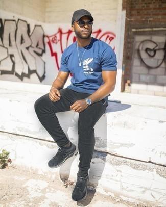 Tendances mode hommes: Essaie d'associer un t-shirt à col rond imprimé bleu avec un pantalon de jogging noir pour une tenue idéale le week-end. Complète ce look avec une paire de chaussures de sport noires.