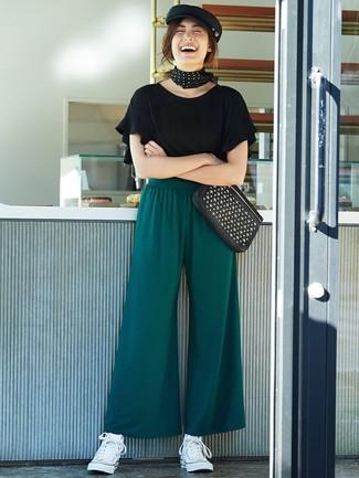 Comment porter: t-shirt à col rond à volants noir, pantalon large vert foncé, baskets montantes en toile blanches, pochette en cuir à clous noire