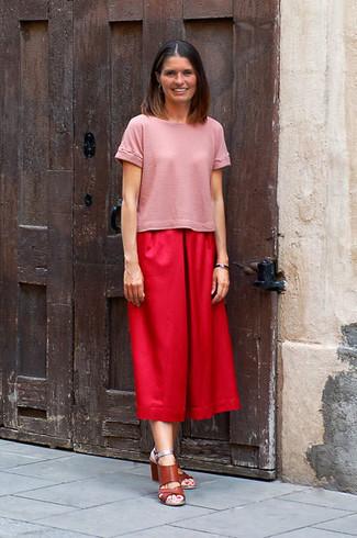 Comment porter: t-shirt à col rond rose, jupe-culotte rouge, sandales à talons en cuir marron