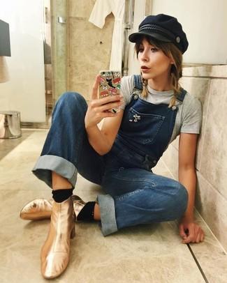 Comment porter: t-shirt à col rond gris, salopette en denim bleue, bottines en cuir dorées, casquette plate noire
