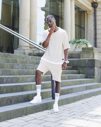 Comment porter: t-shirt à col rond beige, short beige, baskets basses blanches, lunettes de soleil bleu marine