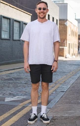 Comment porter des baskets basses en toile noires et blanches quand il fait très chaud: Pour une tenue de tous les jours pleine de caractère et de personnalité pense à opter pour un t-shirt à col rond blanc et un short en denim noir. Une paire de des baskets basses en toile noires et blanches est une option parfait pour complèter cette tenue.