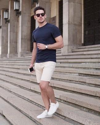 Comment porter un t-shirt à col rond bleu marine: Choisis un t-shirt à col rond bleu marine et un short en denim beige pour affronter sans effort les défis que la journée te réserve. Cet ensemble est parfait avec une paire de des baskets basses en toile blanches.