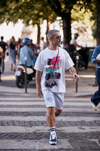 Comment s'habiller après 40 ans quand il fait très chaud: Associe un t-shirt à col rond imprimé blanc avec un short blanc pour une tenue relax mais stylée. Une paire de baskets basses en toile imprimées bleu clair est une option judicieux pour complèter cette tenue.