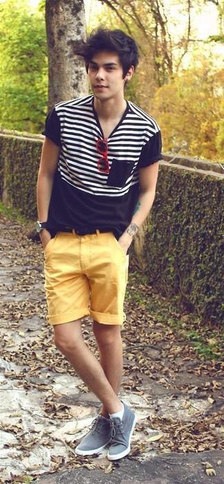 Comment porter: t-shirt à col rond à rayures horizontales noir et blanc, short jaune, bottines chukka en daim grises, ceinture en daim noire