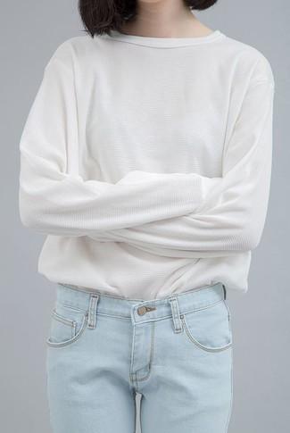 Associe un t-shirt à manche longue blanc avec un jean bleu clair pour une tenue confortable aussi composée avec goût.
