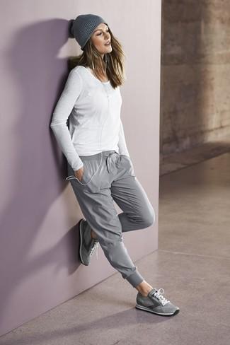 Garde une tenue relax avec un t-shirt à manche longue blanc et un pantalon de jogging gris. D'une humeur créatrice? Assortis ta tenue avec une paire de des chaussures de sport grises.
