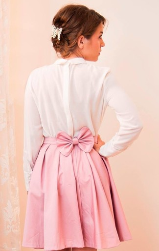 Essaie d'associer un t-shirt à manche longue en soie blanc avec une minijupe plissée rose pour obtenir un look relax mais stylé.