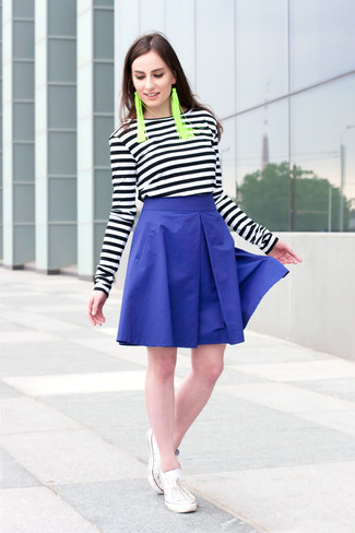 Comment porter: t-shirt à manche longue à rayures horizontales noir et blanc, jupe évasée bleue, baskets basses blanches, boucles d'oreilles vertes