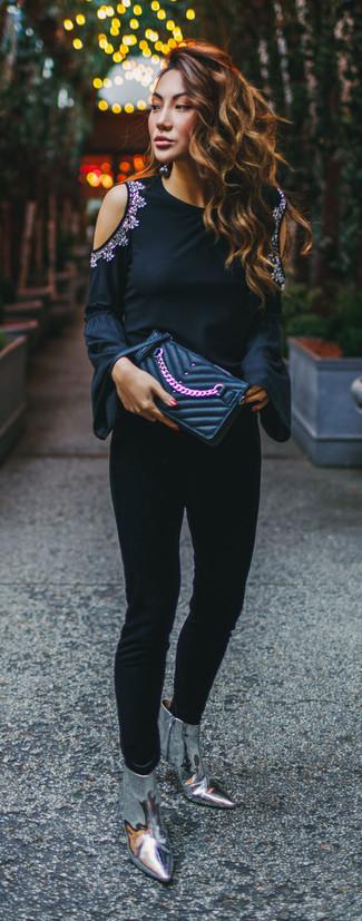 Comment porter: t-shirt à manche longue orné noir, pantalon slim noir, bottines en cuir argentées, pochette en cuir matelassée noire