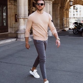Tendances mode hommes: Pense à associer un t-shirt à manche longue beige avec un pantalon chino à rayures verticales bleu pour obtenir un look relax mais stylé. Une paire de baskets basses en cuir blanches et noires s'intégrera de manière fluide à une grande variété de tenues.