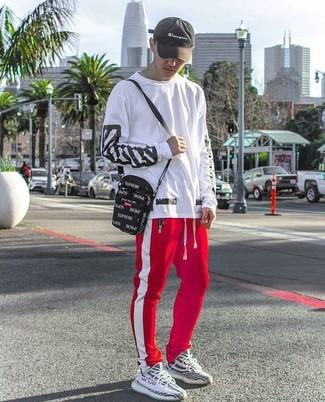Comment porter: t-shirt à manche longue imprimé blanc et noir, pantalon de jogging à rayures verticales rouge et blanc, chaussures de sport noires et blanches, besace en toile noire
