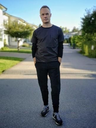 Comment s'habiller après 40 ans: Pense à porter un t-shirt à col rond bleu marine et un pantalon chino noir pour une tenue idéale le week-end. Décoince cette tenue avec une paire de chaussures de sport noires et blanches.