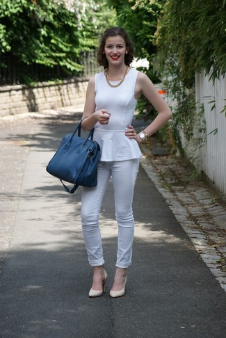 Comment porter: top à basque blanc, jean skinny blanc, escarpins en cuir beiges, sac fourre-tout en cuir bleu