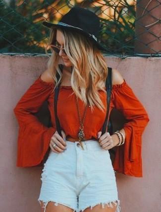 Harmonise un top à épaules dénudées rouge avec un short en denim déchiré bleu clair pour une impression décontractée.