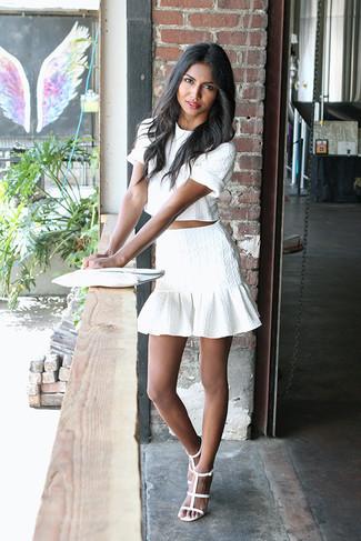 Comment porter une minijupe à volants blanche: Pense à harmoniser un top court blanc avec une minijupe à volants blanche pour créer un look génial et idéal le week-end. Cette tenue se complète parfaitement avec une paire de des sandales à talons en cuir blanches.