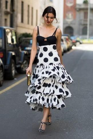 Comment porter: top court noir, jupe mi-longue á pois blanche et noire, escarpins en cuir á pois noirs et blancs, pochette dorée