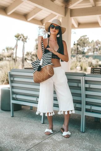 Comment porter: top de bikini en crochet noir, jupe-culotte en lin blanche, sandales plates en toile blanches, sac fourre-tout en toile à rayures horizontales blanc et noir