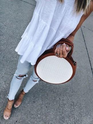 Comment porter: top sans manches blanc, jean skinny déchiré bleu clair, sandales compensées en cuir marron clair, sac bandoulière de paille blanc