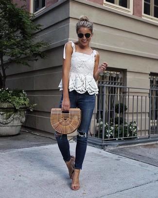 Comment porter: top sans manches en dentelle blanc, jean skinny déchiré bleu marine, sandales à talons en cuir marron clair, pochette de paille marron clair