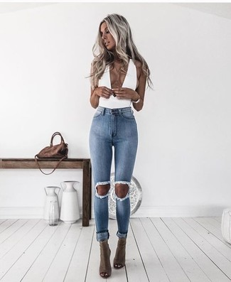 Comment porter: top sans manches blanc, jean skinny déchiré bleu clair, bottines en cuir découpées olive, sac bandoulière en daim marron