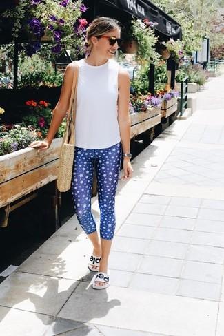 Comment porter: top sans manches blanc, leggings imprimés bleus, sandales plates en cuir blanches, sac fourre-tout de paille beige