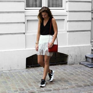 Comment porter: top sans manches noir, minijupe à franges blanche, chaussures de sport noires et blanches, sac bandoulière en cuir rouge