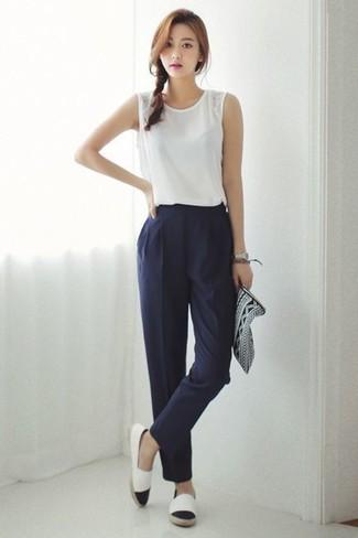 Comment porter: top sans manches blanc, pantalon carotte bleu marine, espadrilles blanches et noires, pochette en cuir imprimée noire et blanche