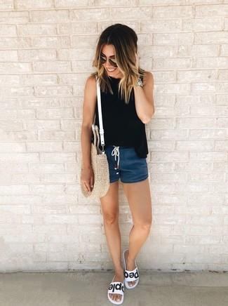 Comment porter: top sans manches noir, short en denim bleu marine, sandales plates en cuir blanches et noires, sac fourre-tout de paille beige