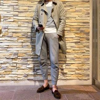 Comment porter: trench beige, pull à col rond à rayures horizontales blanc et bleu marine, pantalon de jogging gris, mocassins à pampilles en daim marron foncé