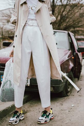 Comment porter: trench beige, t-shirt à col rond imprimé blanc, pantalon carotte blanc, chaussures de sport multicolores