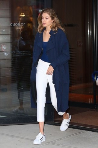 Comment porter: trench bleu marine, débardeur bleu marine, pantalon slim blanc, baskets basses en cuir blanches et noires