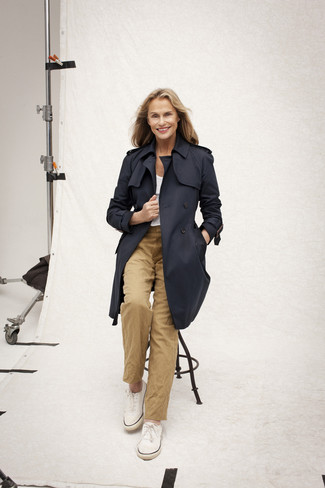 Tenue de Lauren Hutton: Trench bleu marine, T-shirt à col rond blanc, Pantalon chino marron clair, Tennis blancs