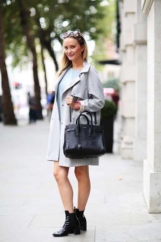 Comment porter: trench gris, robe décontractée bleu clair, bottines en cuir noires, sac fourre-tout en cuir noir