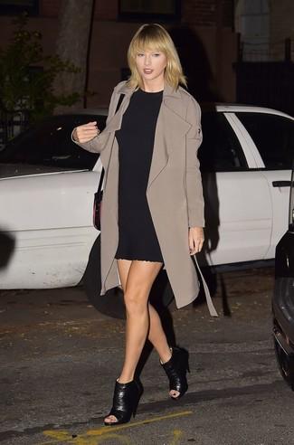 Tenue de Taylor Swift: Trench marron, Robe droite noire, Bottines en cuir découpées noires, Sac bandoulière en cuir noir