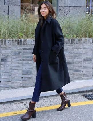 Comment porter: trench noir, pull à col rond noir, jean skinny bleu marine, bottines en cuir marron foncé