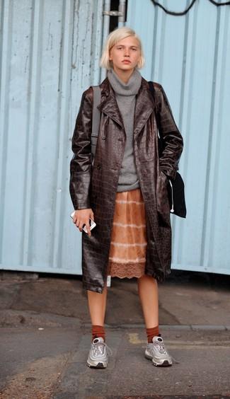 Comment porter: trench en cuir marron foncé, pull à col boule gris, robe nuisette imprimé tie-dye orange, chaussures de sport argentées