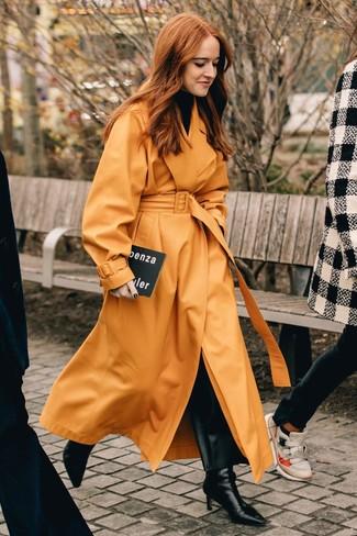 Comment porter: trench en cuir orange, pull à col roulé noir, pantalon large en cuir noir, bottines en cuir noires