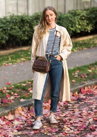 Comment porter: trench beige, t-shirt à col rond à rayures horizontales blanc et bleu marine, jean bleu marine, baskets basses en toile blanches