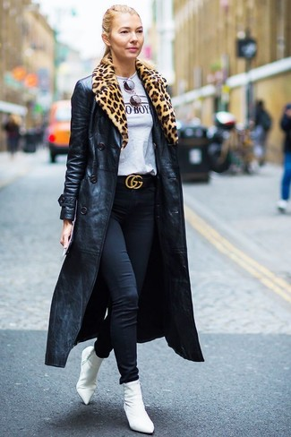Comment porter: trench en cuir noir, t-shirt à col rond imprimé gris, jean skinny noir, bottines élastiques blanches