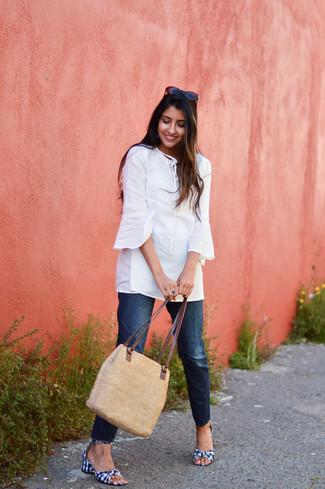 Comment porter: tunique blanche, jean bleu marine, sandales à talons en toile en vichy bleu marine et blanc, sac fourre-tout de paille marron clair